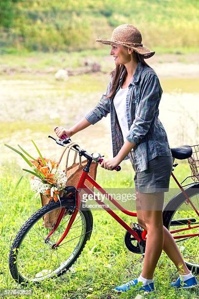 Young woman with bicycle by the river