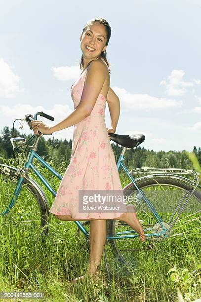 Young woman with bicycle in field, portrait