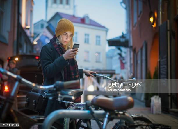 young woman with bicycle looking at smartphone at night - alleen één jonge vrouw stockfoto's en -beelden
