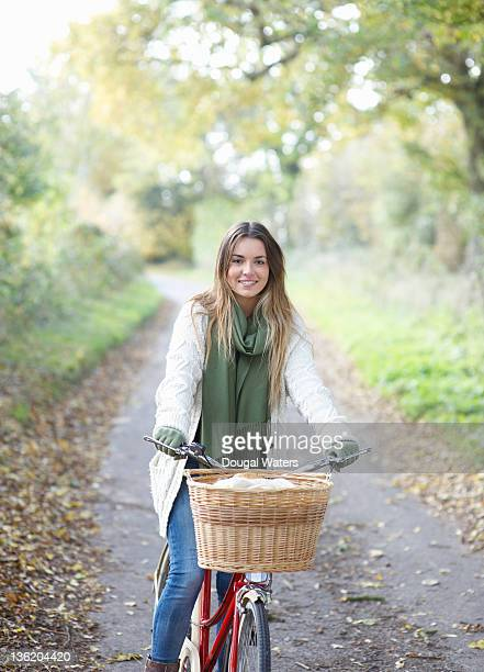 Young woman with bicycle on country road.