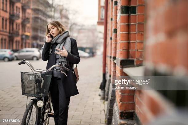 Young woman with bicycle on the phone