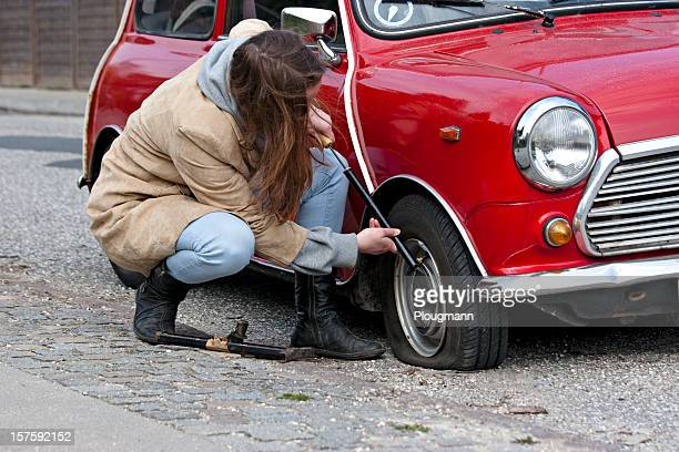 Young woman with bicycle pump and punctured tire