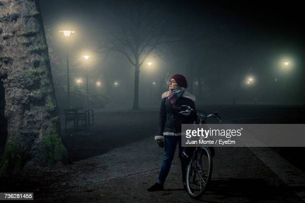 Young Woman With Bicycle Standing On Footpath Amidst Illuminated Street Lights At Park During Winter
