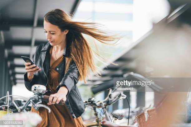 young woman with bicycle using cell phone in the city - radfahren stock-fotos und bilder