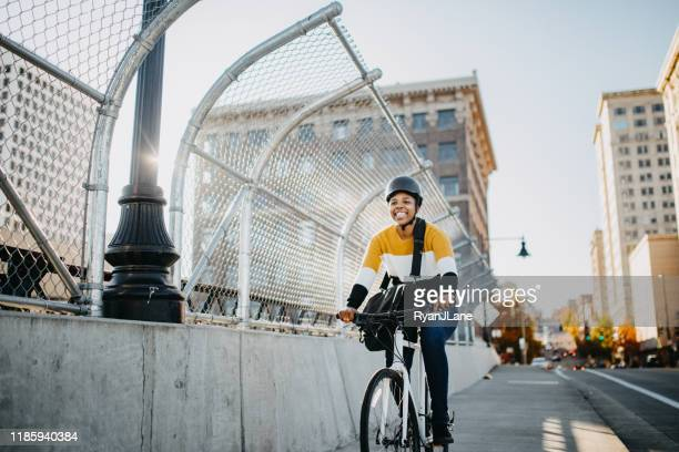 young woman with bike and messenger bag in the city - cycling helmet stock pictures, royalty-free photos & images