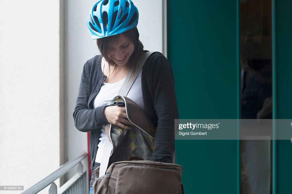 Young woman with bike helmet going out of the flat, Freiburg im Breisgau, Baden-Württemberg, Germany : Stock-Foto