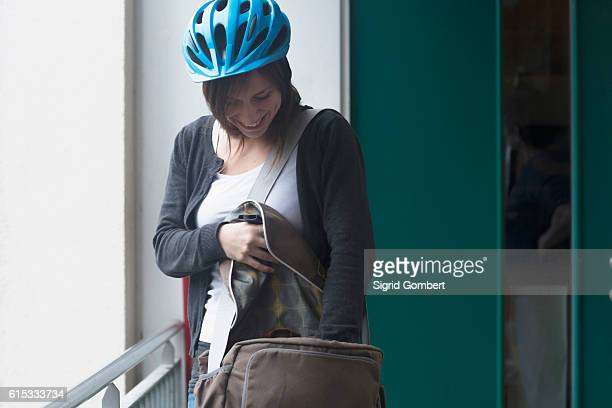 young woman with bike helmet going out of the flat, freiburg im breisgau, baden-württemberg, germany - sigrid gombert stock-fotos und bilder