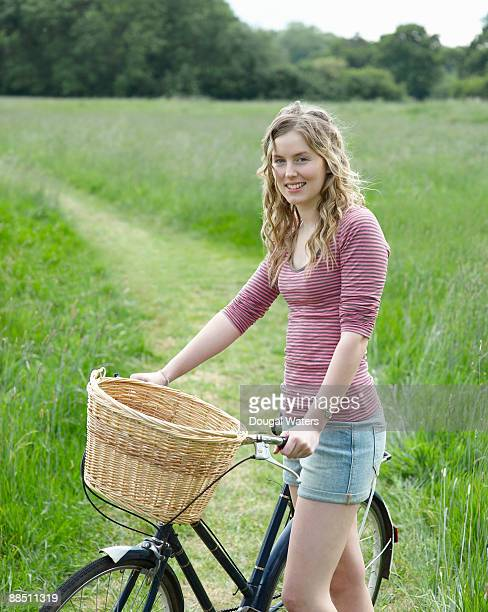 Young woman with bike in countryside.