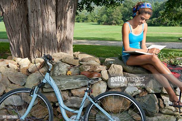 Young Woman with Bike Relaxing and Reading