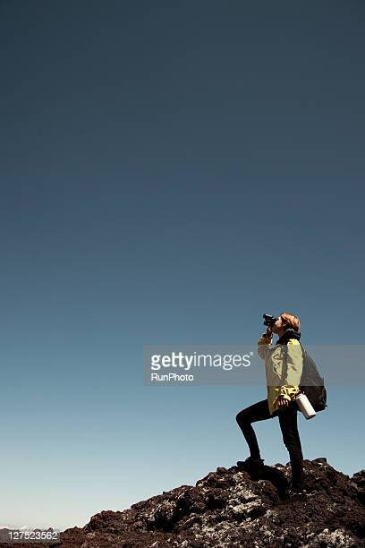 young woman with binoculars in the mountains
