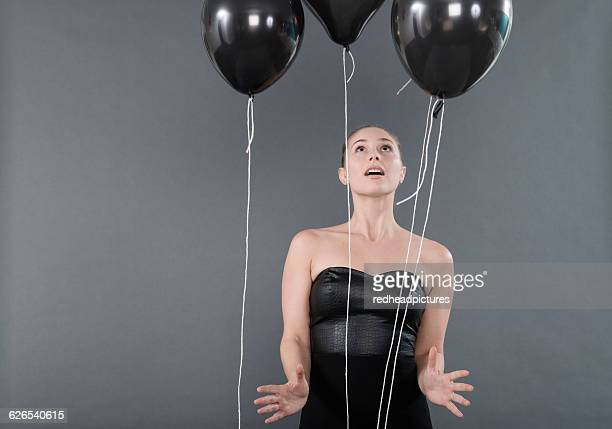 Young woman with black balloons, grey background