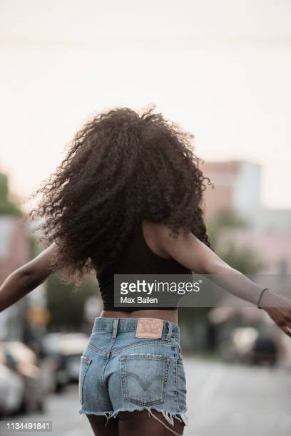 young woman with black hair and arms out - denim shorts stock pictures, royalty-free photos & images