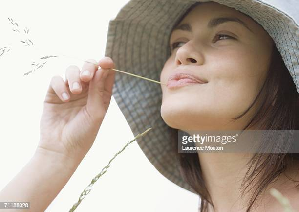 Young woman with blade of grass in mouth
