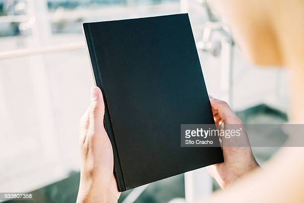 Young woman with blank book in her hands
