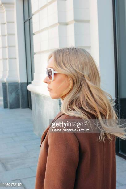 young woman with blond hair standing on sidewalk - eastern european descent stock pictures, royalty-free photos & images