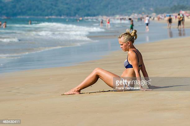 A young woman with blond hair wearing a bikini is sitting in the sand of Calangute Beach in the former Portuguese colony Goa