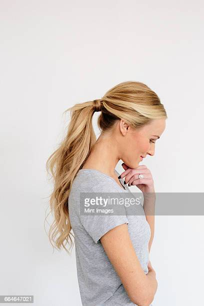 a young woman with blonde hair in a grey shirt, one hand on her chin. - ponytail stock pictures, royalty-free photos & images
