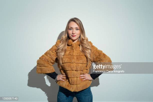 young woman with blonde hair in yellow fur coat - overcoat stock pictures, royalty-free photos & images