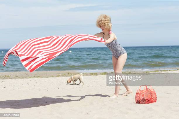 Young woman with blowing beach towel at seaside