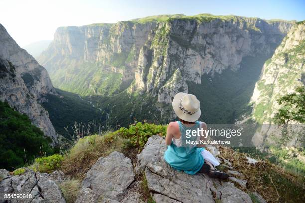 young woman with blue dress and hat sitting over vikos gorge, timfy mountain, zagoria / epirus, greece - epirus greece stock pictures, royalty-free photos & images