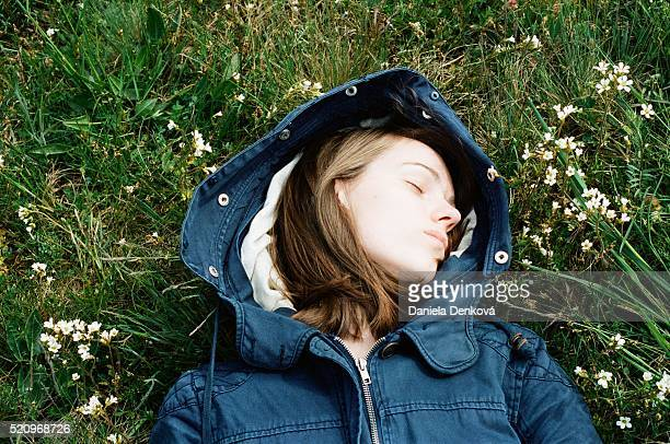 Young woman with blue hood sleeping in meadow
