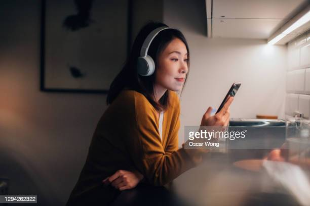 young woman with bluetooth headphones listening to music on smartphone - listening stock pictures, royalty-free photos & images