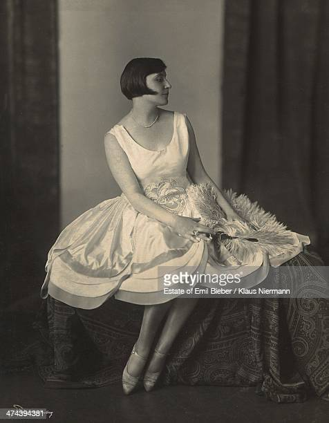 Young woman with bobbed hair modelling a knee-length day dress with a scalloped hem, circa 1920.