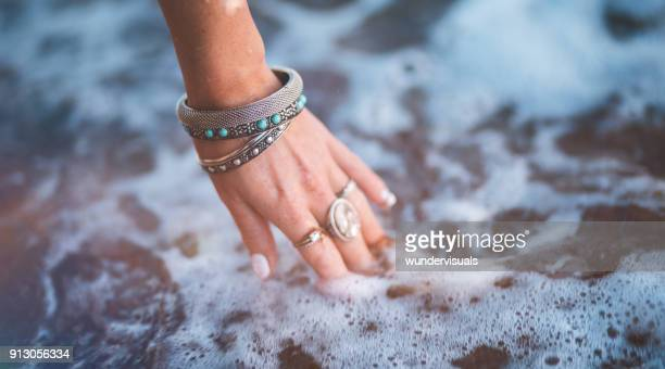 young woman with boho style jewelry at the beach - bracelet photos stock pictures, royalty-free photos & images