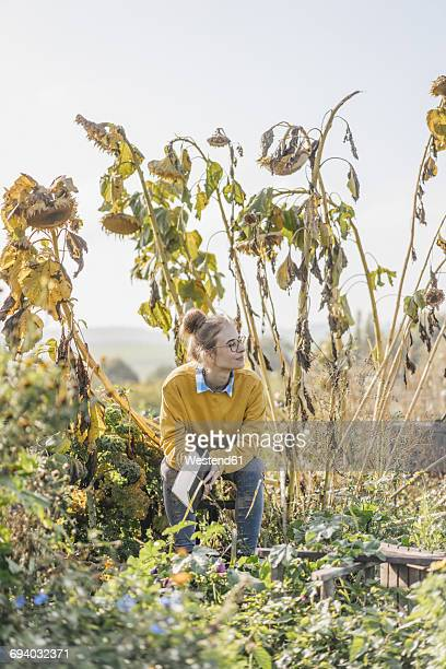 Young woman with book relaxing in cottage garden