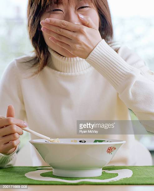 Young woman with bowl of noodles, covering mouth with hand, laughing