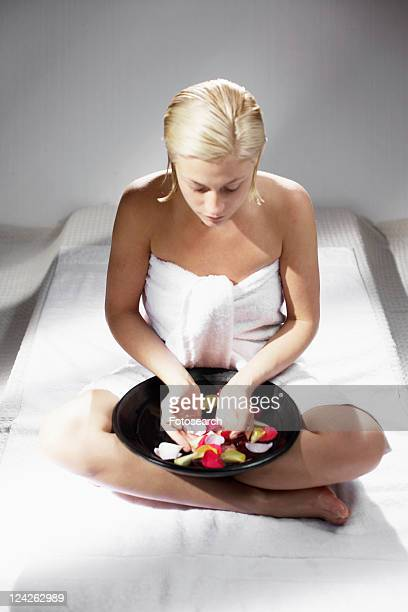 Young woman with bowl of rose water