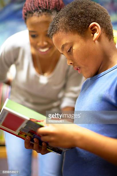 young woman with boy reading book - teacher bending over stock photos and pictures