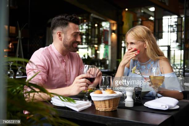 young woman with boyfriend laughing at restaurant table - romance fotografías e imágenes de stock