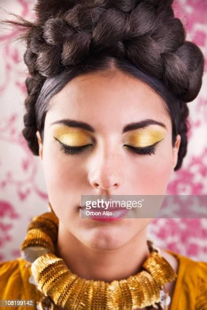 Junge Frau mit geflochtenen Brötchen und Make-Up der Augen schließen