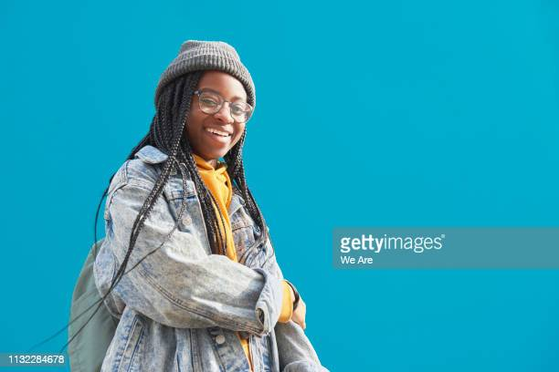 young woman with braided hair smiling. - street style stock pictures, royalty-free photos & images