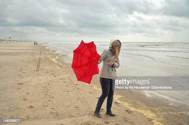young woman with broken red umbrella - mujeres de mediana edad fotografías e imágenes de stock