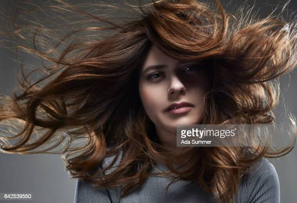young woman with brown long windblown hair