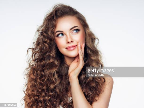 young woman with brown voluminous and curly hair - curly hair stock pictures, royalty-free photos & images