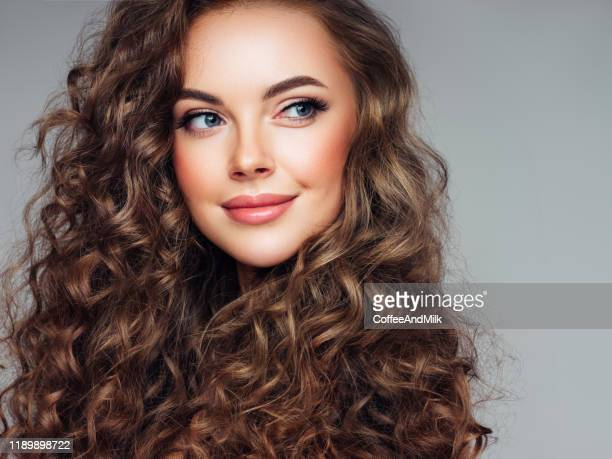 young woman with brown voluminous and curly hair - wavy hair stock pictures, royalty-free photos & images
