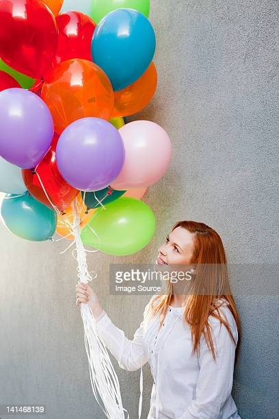 Young woman with bunch of balloons