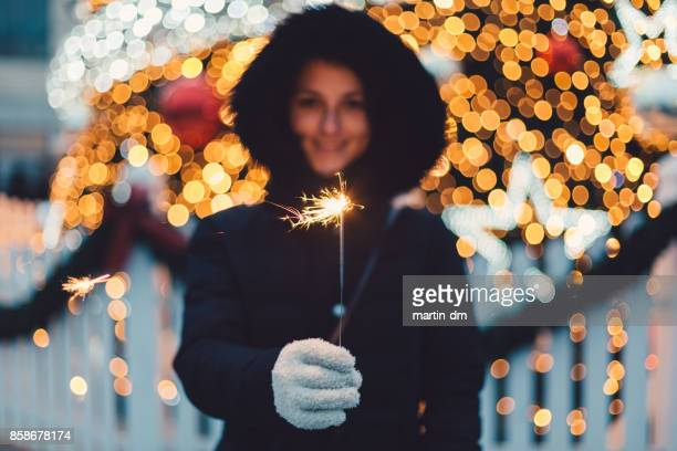 Young woman with burning sparkler for Christmas