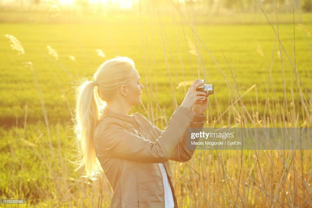 Young Woman With Camera Standing In Field : Photo