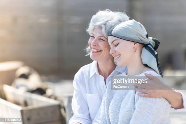 junge frau mit krebs umarmt ihre mutter - cancer illness stock-fotos und bilder