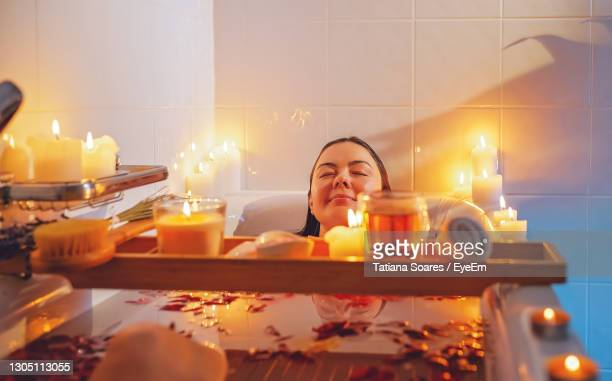 young woman with candles on table - candle stock pictures, royalty-free photos & images