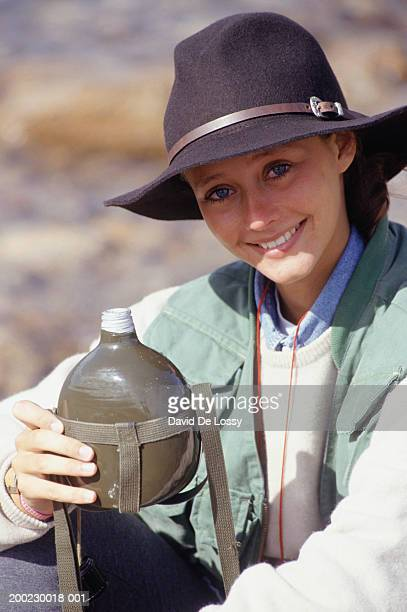 Young woman with canteen and felt hat sitting outdoors, portrait