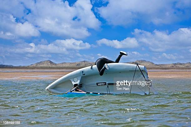 young woman with capsized dinghy. - sinking stock pictures, royalty-free photos & images