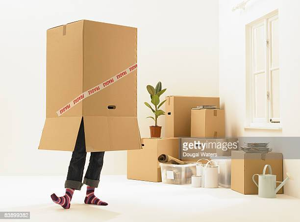 Young woman with cardboard box on head.