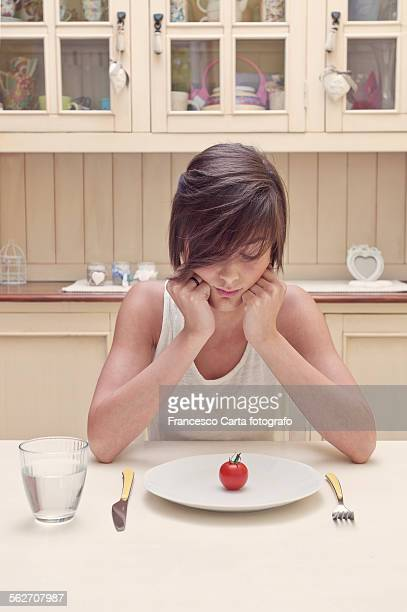 young woman with carrot on a plate - magersucht stock-fotos und bilder