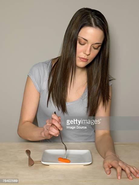 Junge Frau mit Karotte auf einer Platte