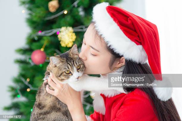 young woman with cat against christmas tree - cat with red hat stock pictures, royalty-free photos & images
